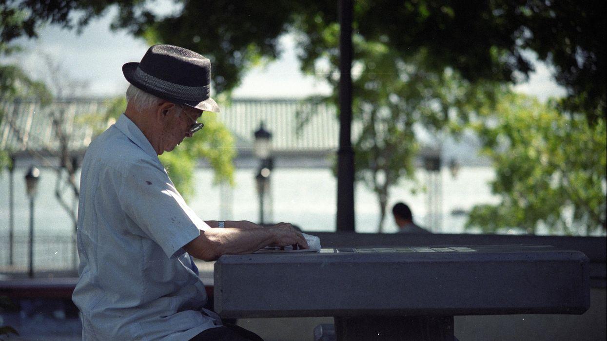 Egy idős férfi egy sakktábla felett ül