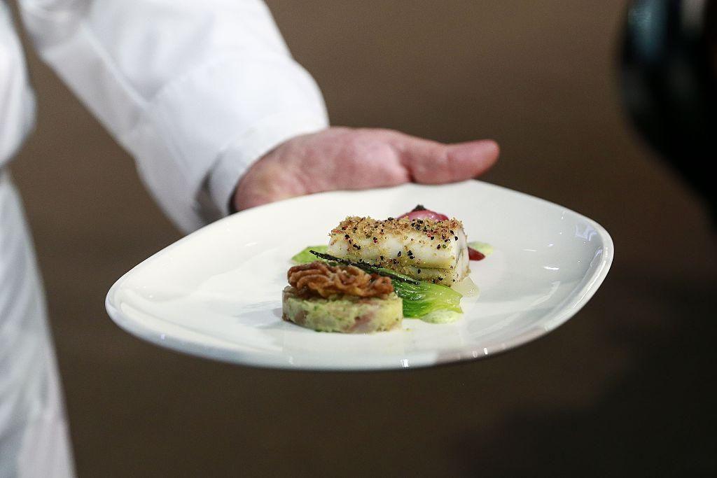 Egy szakács egy tányér halat tart a kétévente megrendezett Bocuse d'Or szakács világbajnokságon a budapesti HUNEXPO Vásárközpontban 2016 májusában.