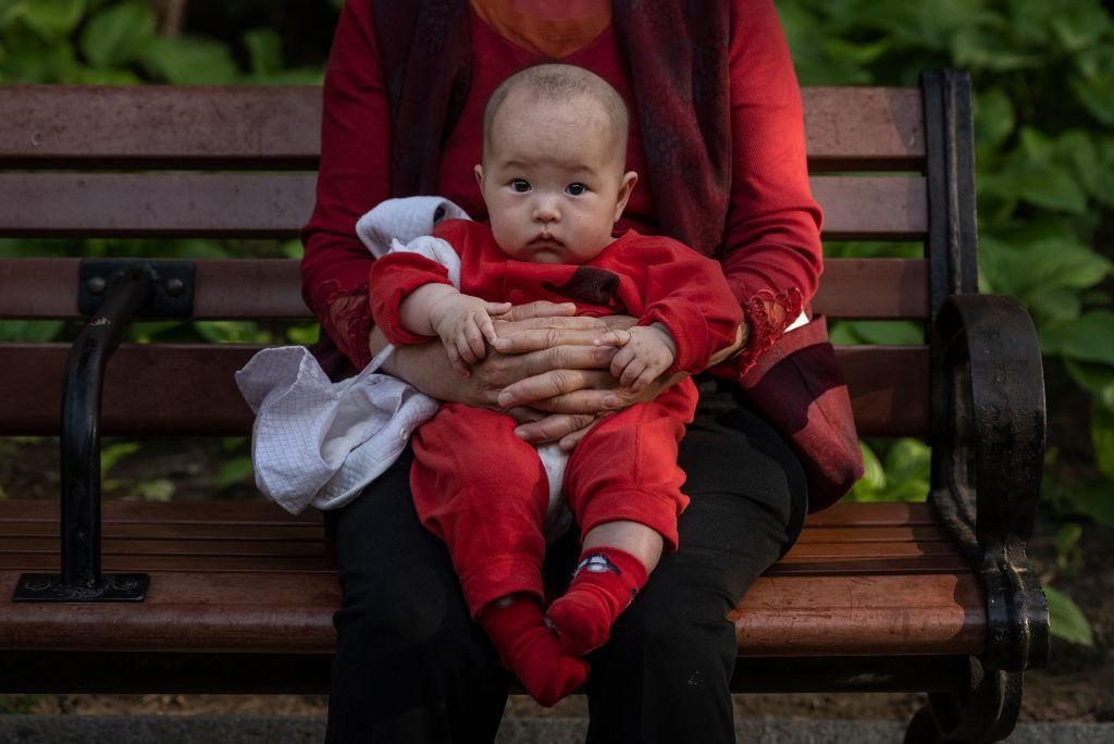 Egy nő karjában tartja gyermekét Pekingben