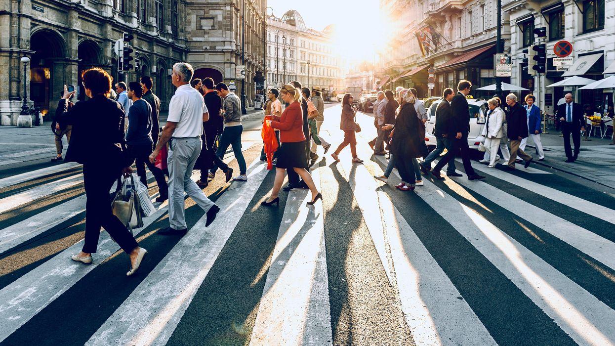 Embertömeg sétál át egy gyalogosátkelőn